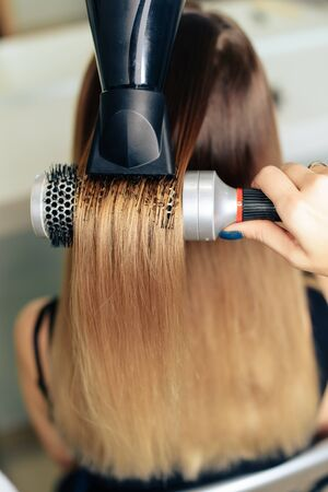stylists work with the hair of a girl in a beauty salon