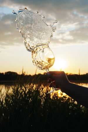 a glass of water on the background of the river and the sunset 1 Standard-Bild