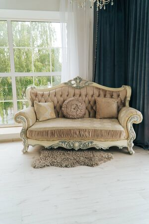 beautiful expensive beige sofa against a white wall in an empty room Zdjęcie Seryjne