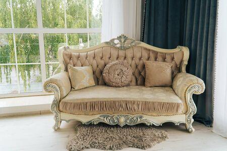 beau canapé beige cher contre un mur blanc dans une pièce vide Banque d'images
