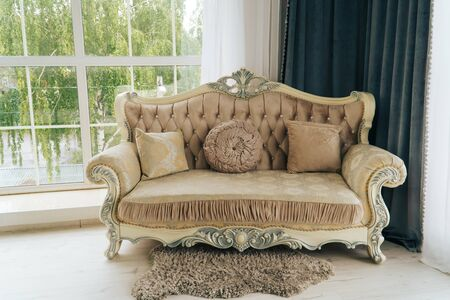 beautiful expensive beige sofa against a white wall in an empty room Reklamní fotografie
