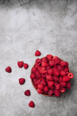 clay plate with tasty bright raspberries on a gray background