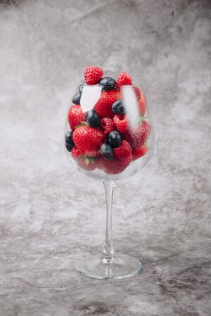 ripe juicy tasty berries on a gray background in a wine glass Stock Photo