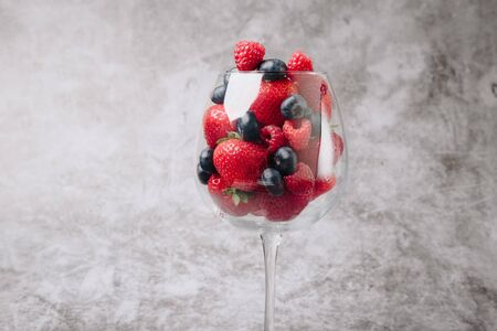 ripe juicy tasty berries on a gray background in a wine glass 1 Stock Photo