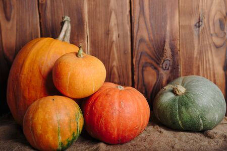 autumn set of pumpkins and dried leaves on a wooden background