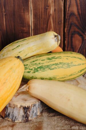 yellow long zucchini on a wooden background