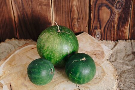 several mini watermelons on a wooden background Фото со стока