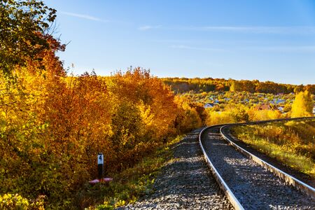 rails going into the distance against the backdrop of an autumn landscape