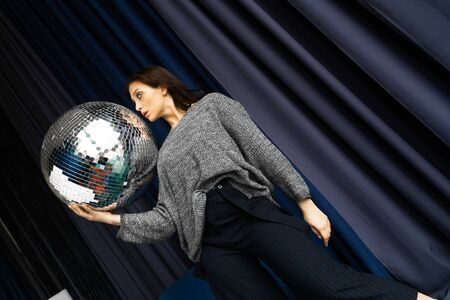 beautiful girl in gray with a big disco ball in her hands