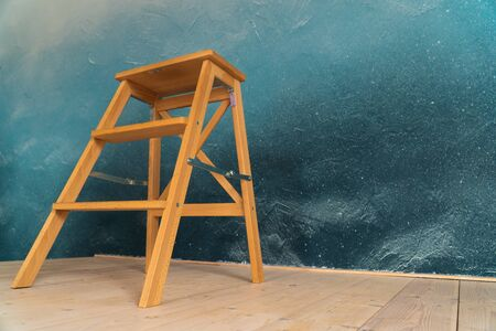 wooden stepladder on the background of flooring from boards and a dark wall Фото со стока - 133782915