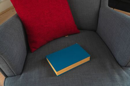 gray armchair with red pillow and blue book