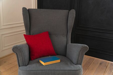 gray armchair with red pillow and blue book Фото со стока - 133782959