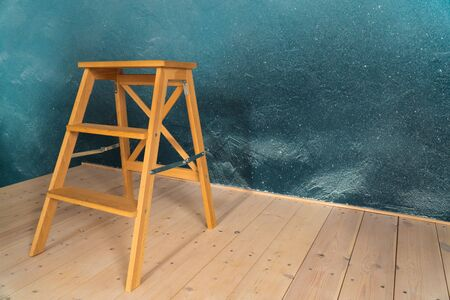 wooden stepladder on the background of flooring from boards and a dark wall