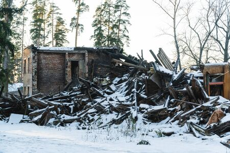 an old abandoned house in a pine winter forest Фото со стока