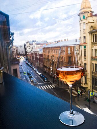 a glass of wine on the background of St. Petersburg streets