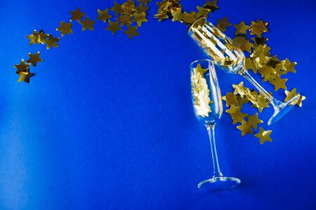 champagne glasses with gold stars on a blue background Фото со стока