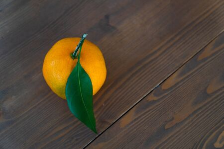 mandarin with leaf on a wooden surface 1
