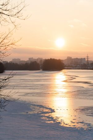 sunset over a river covered in ice and snow 1