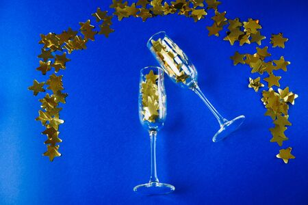 champagne glasses with gold stars on a blue background 1 Фото со стока - 136863554