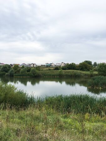 summer landscape with green grass and a small pond Фото со стока - 136863590