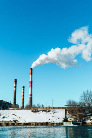 Smoking pipes of the plant against the blue sky, white smoke from the pipes Stock Photo