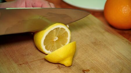 a girl cuts a juicy ripe vitamin yellow lemon with a knife on a wooden Board