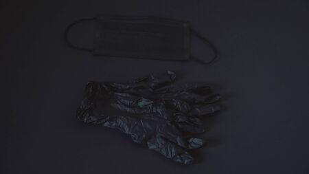 Black medical mask and black gloves on a black background Archivio Fotografico