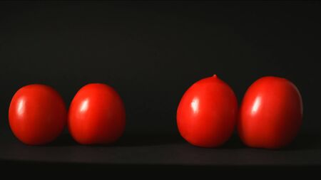 Red fresh tomatoes on a black background Archivio Fotografico