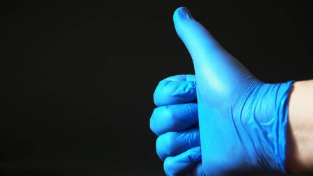 A blue gloved hand gives a thumbs up
