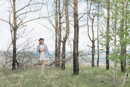 young beautiful girl in a denim jacket in the forest in summer with dry trees Archivio Fotografico