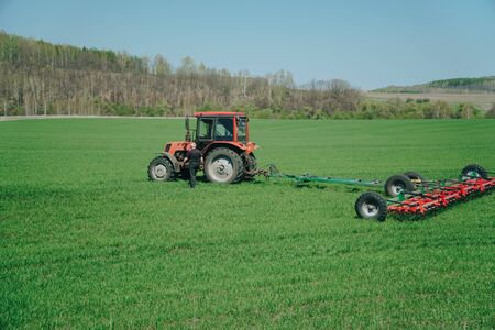 The tractor is working on a green spring field. Agriculture with cereal crops 1