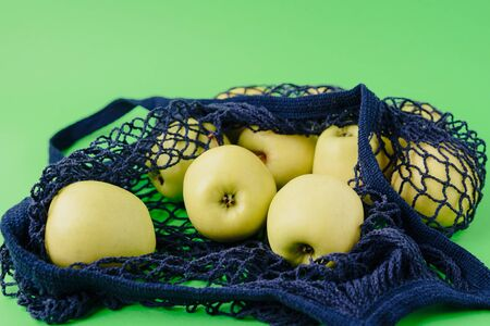 blue string bag with green apples on a green background Archivio Fotografico