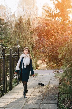 beautiful fashionable young girl in the Park in autumn in Sunny weather 1