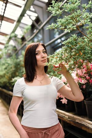 A beautiful young girl walks through an old greenhouse. Woman in the Botanical garden