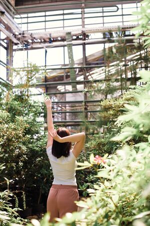 A beautiful young girl walks through an old greenhouse. Woman in the Botanical garden 1