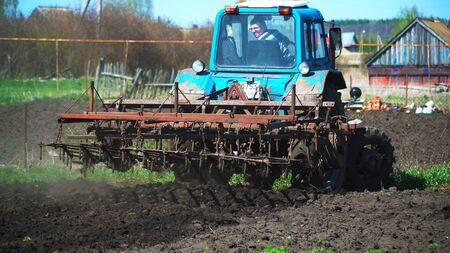 The tractor cultivates and cuts furrows in the field. Tractor work in the black soil field in the village 1