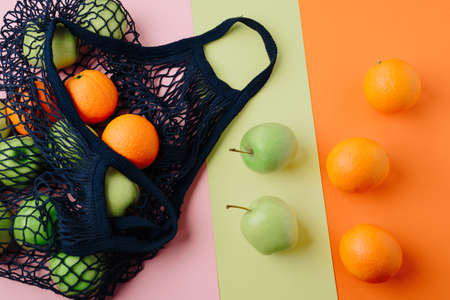 apples and oranges in a blue string bag on a colored background. Fruits in a grid on multicolored backgrounds