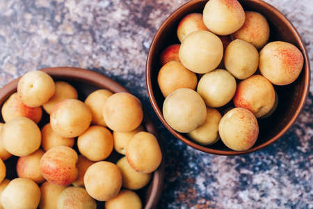 Lots of ripe yellow apricots close up in a crockery on the table