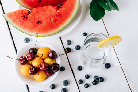 Summer still life of fresh fruit and berries on a white wooden surface Reklamní fotografie