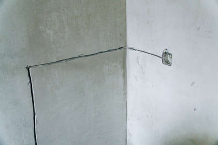 Holes in the concrete wall in the room for sockets