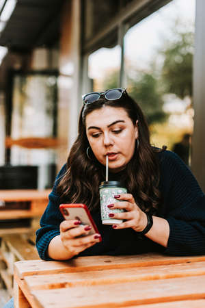 Portrait of a young adult girl with a Cup of coffee near a cafe in good autumn weather Фото со стока