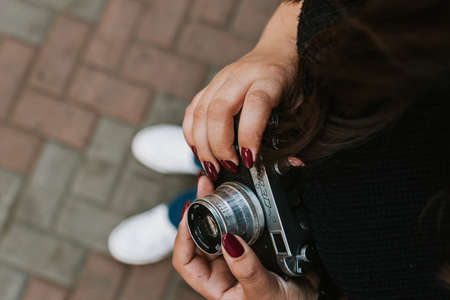 Young adult girl holding vintage camera outdoors Фото со стока