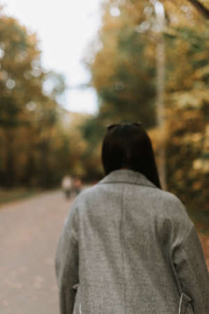 Beautiful woman in a gray coat on an autumn alley
