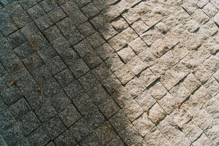 Gray stone pavement texture. Paving stones with yellow autumn leaves