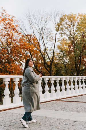 Portrait of a beautiful adult young woman on the background of autumn in the Park Фото со стока