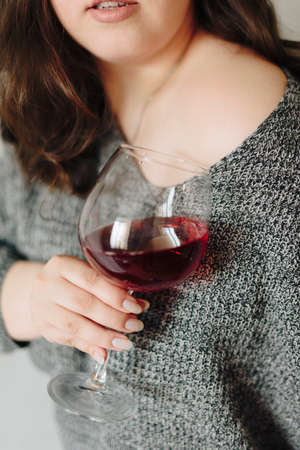 close-up of a girl in a grey sweater with a glass of red wine