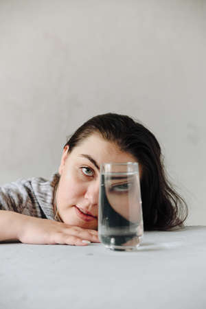 beautiful girl at the table on a gray background in her hands with a glass of water. Girls face through a glass of water