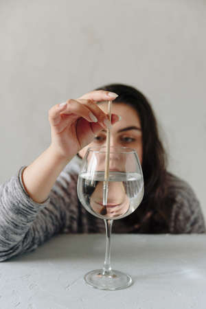 beautiful girl at the table with a wine glass with water and a paint brush Фото со стока