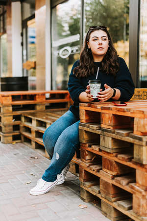 Portrait of a young adult girl with a Cup of coffee near a cafe in good autumn weather Standard-Bild