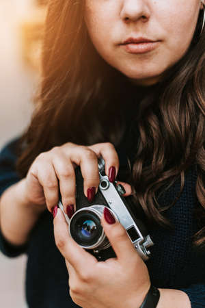 Portrait of young adult girl holding vintage camera outdoors